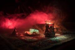 在玻璃的阿拉伯茶与在一张地毯的东部快餐在与光和烟的黑暗的背景 东部茶概念 空的空间 图库摄影