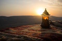 在玻璃的阿拉伯茶在一张东部地毯 东部茶概念 Armudu传统杯子 背景波罗的海日落 选择聚焦 免版税库存图片