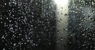 在玻璃的雨珠在路灯柱前面的晚上 股票录像