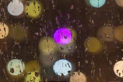 在玻璃的雨珠色的光背景在bokeh a的 免版税库存图片