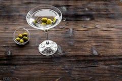 在玻璃的马蒂尼鸡尾酒鸡尾酒用在底部的橄榄在黑暗的木背景顶视图copyspace 库存图片