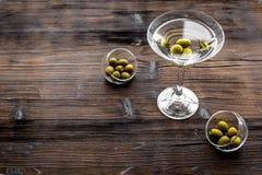 在玻璃的马蒂尼鸡尾酒鸡尾酒用在底部的橄榄在黑暗的木背景顶视图copyspace 免版税库存照片