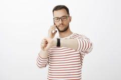 在玻璃的,谈话在智能手机和看手表的严肃的悦目商人画象,处理 免版税库存图片