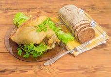 在玻璃盘和黑面包的被烘烤的火腿飞腓节此外 免版税图库摄影