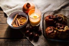 在玻璃盘子的烤苹果用栗子、桂香、桔子和石榴 库存图片
