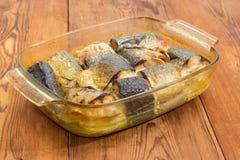 在玻璃砂锅平底锅的被烘烤的鲭鱼在老桌特写镜头 库存图片