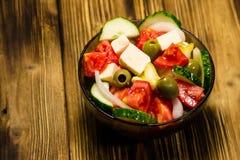 在玻璃碗的希腊沙拉在木桌上 库存照片