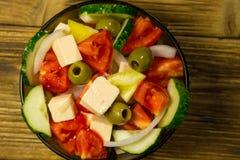 在玻璃碗的希腊沙拉在木桌上 免版税库存照片