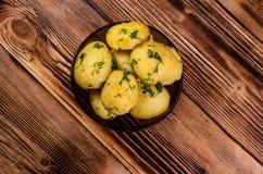 在玻璃碗的煮的年轻土豆在木桌上 顶视图 库存照片