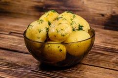 在玻璃碗的煮的年轻土豆在木桌上 免版税库存图片