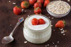 在玻璃碗的白色在土气的酸奶有匙子的和starwberries 免版税库存照片