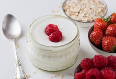 在玻璃碗的白色在白色的酸奶有匙子的和starwberries 库存照片