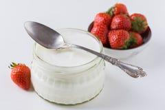 在玻璃碗的白色在白色的酸奶有匙子的和starwberries 库存图片