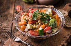 在玻璃碗的菜沙拉用硬花甘蓝和蕃茄在黑暗 图库摄影