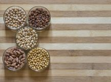 在玻璃碗的被分类的豆类,在一块砧板 免版税库存图片