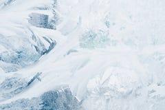 在玻璃窗的结冰的样式在冬天和设色在蓝色 免版税库存照片
