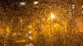 在玻璃窗的被弄脏的雨珠 从窗口的看法 图库摄影