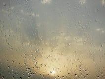 在玻璃窗的雨水下落在与太阳焕发的一个多云天早晨在云彩后的背景捉迷藏怒视 库存图片