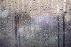 在玻璃窗的雨珠与夜光bokeh关闭为背景 免版税库存图片