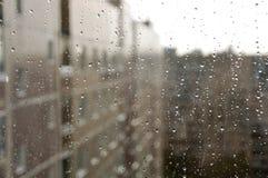 在玻璃窗的雨珠反对城市背景 免版税库存图片