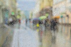 在玻璃窗的雨珠,无法认出的人民在路走在雨天 从窗口的看法在城市街道上,被弄脏 库存图片