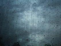 在玻璃窗背景的雨水下落 免版税库存照片