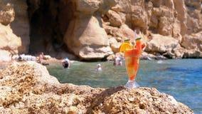 在玻璃立场的异乎寻常的鸡尾酒在红海背景的礁石海滩  ?? 股票录像