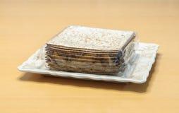 在玻璃纸包裹Pesach广场形状的包装未发酵的面包包裹的在桌上的一块板材说谎 免版税库存图片