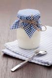 在玻璃罐和匙子的自创牛奶酸奶在表 免版税库存图片