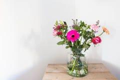 在玻璃花瓶,在木桌白色墙壁上的春天装饰的五颜六色的花 库存图片
