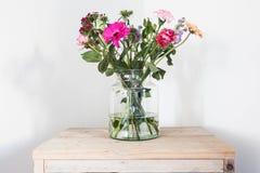 在玻璃花瓶,在木桌白色墙壁上的春天装饰的五颜六色的花 免版税库存图片