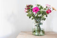 在玻璃花瓶,在木桌白色墙壁上的春天装饰的五颜六色的花 图库摄影