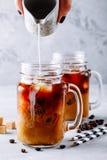在玻璃金属螺盖玻璃瓶的被冰的咖啡用牛奶和冰块 免版税库存照片