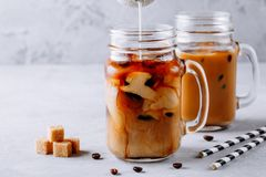 在玻璃金属螺盖玻璃瓶的被冰的咖啡用牛奶和冰块 库存照片