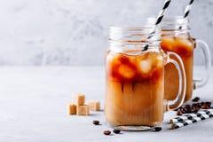 在玻璃金属螺盖玻璃瓶的被冰的咖啡用牛奶和冰块 免版税库存图片
