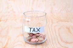 在玻璃金钱瓶子的硬币有税标签的,财政概念 葡萄酒木背景 免版税库存图片