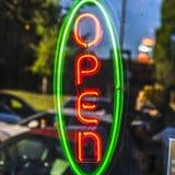 在玻璃门的氖开放标志与反射 免版税库存图片
