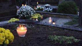 在玻璃黑地面坟墓后的烛光焰在公墓 4K 股票录像