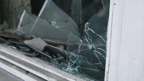 在玻璃,在轰击以后的一个残破的窗口,枪射击的弹孔 对公开或私有的破坏或损伤 股票视频