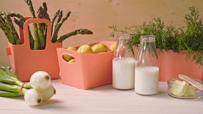 在珊瑚容器和瓶的春天年轻菜用在桌上的牛奶 股票视频