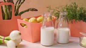 在珊瑚容器和瓶的春天年轻菜用在桌上的牛奶 影视素材