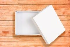 在珊瑚木背景的被打开的白色纸板箱 图库摄影