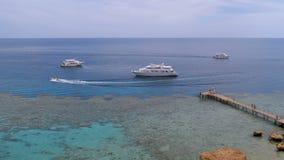 在珊瑚海滩的全景与码头和游船在红海礁石的 ?? 股票录像
