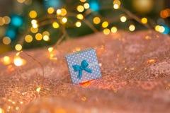在珊瑚背景的NBlue礼物反对用金子和蓝色球装饰的一棵被弄脏的新年树 库存图片