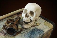 在珍宝地图的海盗头骨 库存照片