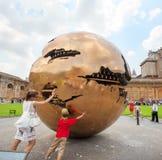 在球形附近的人们在球形内在Pinecone的庭院里 免版税库存图片