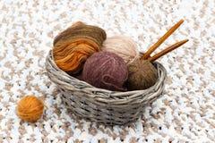 在球的五颜六色的毛线和卷和木针在结辨的篮子在 图库摄影