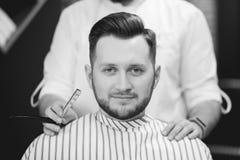 在理发、胡子和头发以后的有胡子的人在理发椅 免版税库存照片
