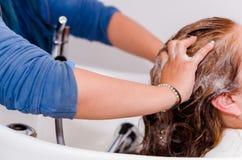 在理发交谊厅里面的按摩,洗与好的香波一根长的头发的手 库存图片