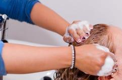 在理发交谊厅里面的按摩,洗与好的香波一根长的头发的手 库存照片